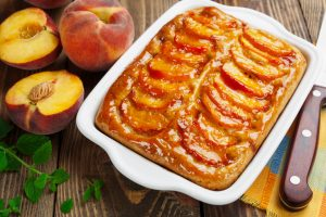 GLAZED PEACH COBBLER AND FRESH PEACHES ON CUTTING BOARD WITH KNIFE
